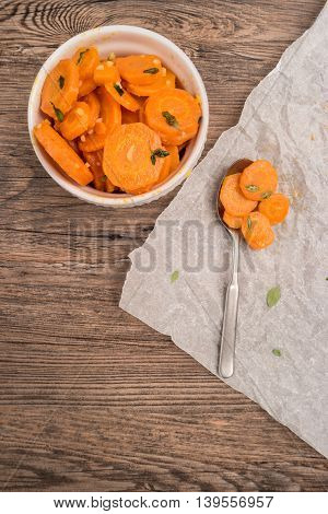 Healthy organic sauteed carrots in a bowl garnished with thyme. Top view