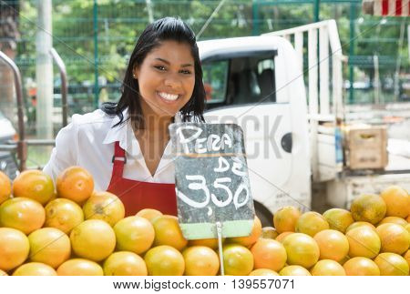 Happy mexican saleswoman with oranges outdoor on a farmers market