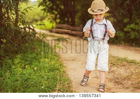 boy stands in the forest on footpath