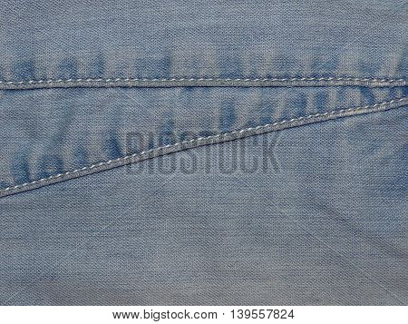 light blue denim fabric sewn into her seams , close up
