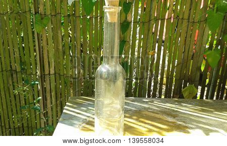Narrow tall dirty clear glass bottle with cork