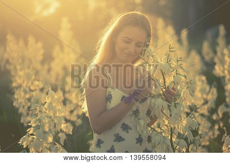Princess. Young Beautiful Pretty Woman Posing In Long Dress Against In The Field With White Flowers