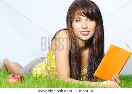 beautiful woman lays on green field and reads book.