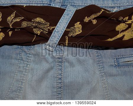 light blue denim fabric sewn into her seams and a brown scarf place of the belt
