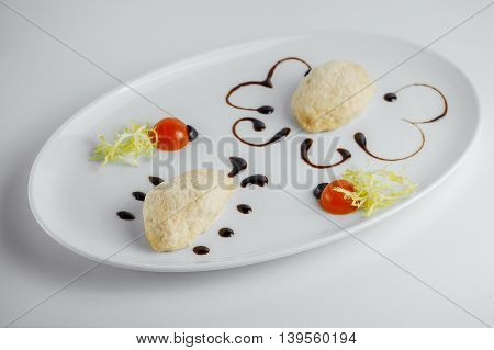 Chicken Cutlet With Sauce, Tomato Slices And Olives On A White Plate