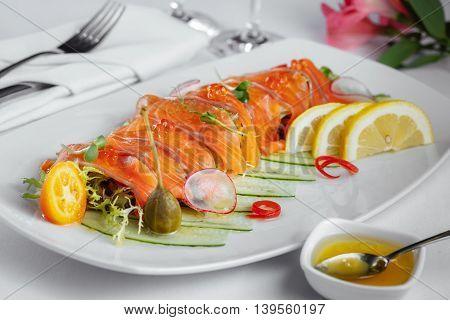 Salmon With Lemon, Cucumbers And Greens On A White Plate