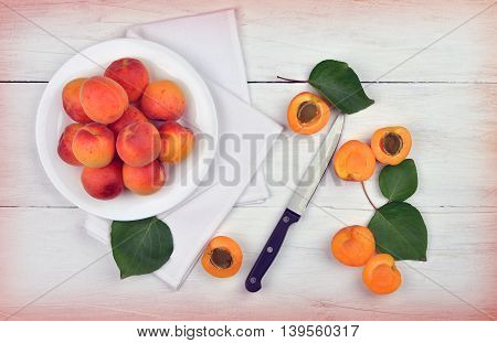 Apricots. Dish of harvested apricots on a wooden surface top view rustic style. Appetizing background of summer fruits. Art processing. Toning.