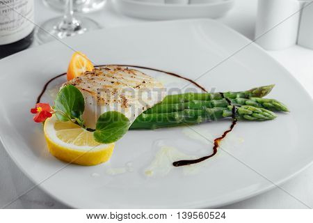 Fish With Lemon, Asparagus And Sauce On A White Plate