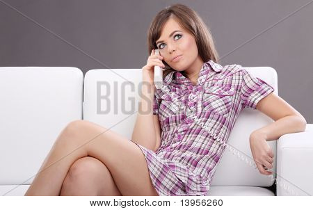 Relaxed young woman sitting on white sofa  talking on cell phone