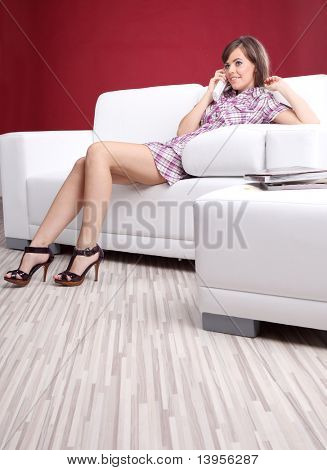 Young woman laying on couch talking on  telephone