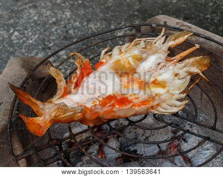 Grilling fresh big shrimps on the coals