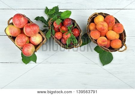 Apples plums apricots in baskets on old painted wooden background. Top view. The harvest of summer fruits. Gardening. Nice result of labor. Background - healthy eating. Diet. Vitamins.