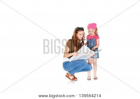 Happy woman and little girl preparing for the journey. Mom and daughter study the map and choose a route of travel. Isolated on white background.