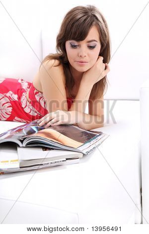young woman  reading magazine on sofa
