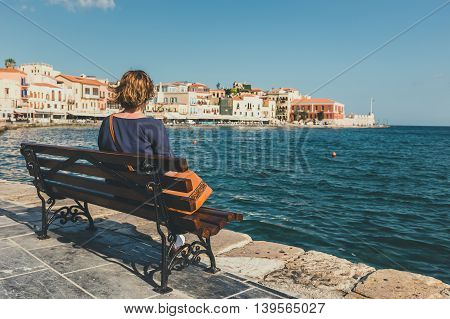 young woman sitting on the bench and looking at old port in Chania Crete Greece