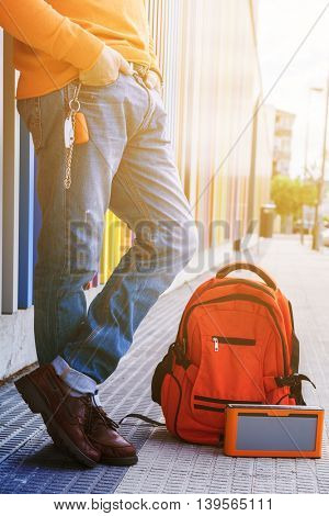 Street fashion. Male outdoor portrait. Man standing near colored building in jeans, orange sweater, blue tooth loudspeaker and backpack, detail. Image toned.