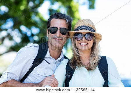 Happy couple wearing sunglasses on street in city