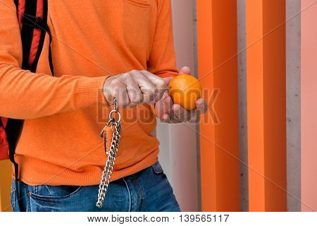 Male outdoor portrait. Man standing near colored building with orange, keychain, car keys knife, detail. Image toned.