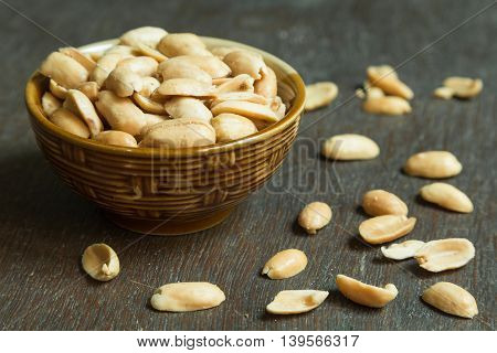 Roasted peeled salted peanuts in rustic bowl on wooden background (focus on peanut in bowl)