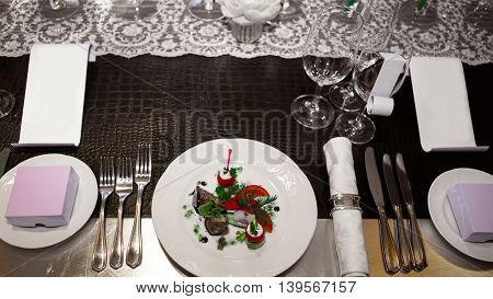 Table with dishes on a Banquet table covered in crocodile skin. Glasses and plates, forks and knives, napkins and buttons for a luxurious evening celebration. Luxury festive table.