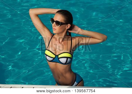woman near the pool wearing glasses and swimsuit tans and relaxing on vacation healthy athletic body