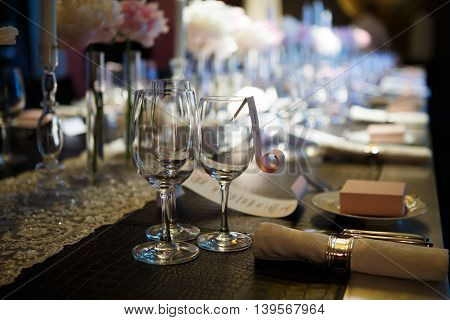Wine glasses on table covered in, glasses and plates, forks and knives, napkins and buttons for a luxurious celebration in anticipation of guests, luxury festive table.