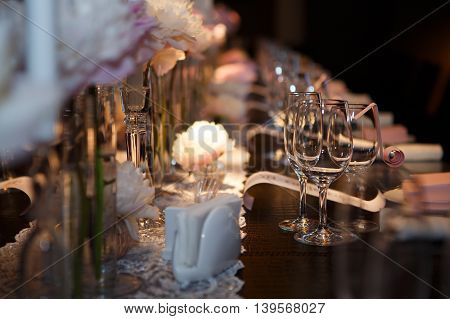 Banquet table covered in, glasses and plates, forks and knives, napkins and buttons for a luxurious celebration in anticipation of guests, luxury festive table.