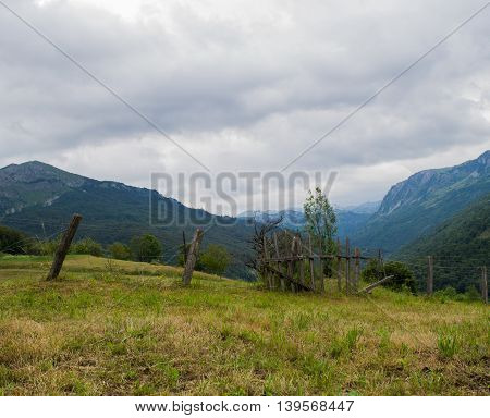 Old gate on field with mountains in the back