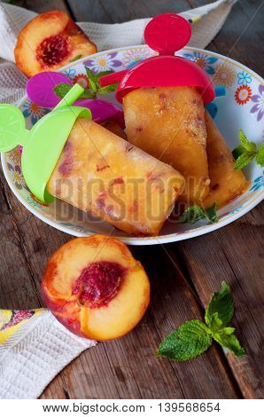 Peach ice lollies with colored sticks on a kitchen napkin with mint leaves