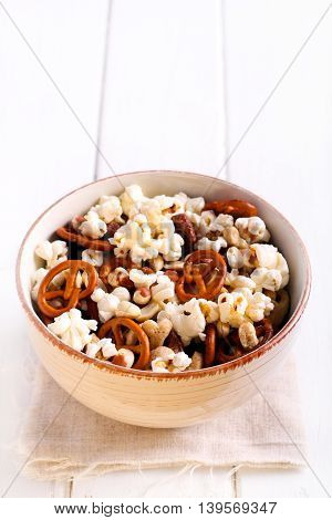 Mix of snacks - pop corn nuts pretzel - in a bowl