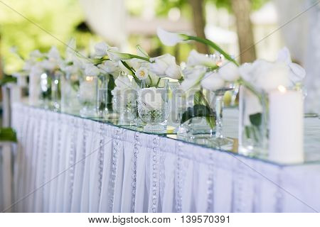 Beautiful restaurant interior table decoration for wedding. Flower Wedding Table Decoration. White calla lilies and tulips in vases. Candles.