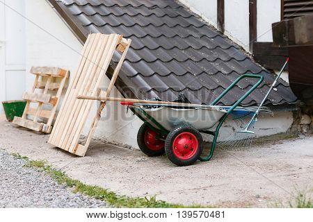 garden tools rakes trolley summer spring. red wheels. basement roof.