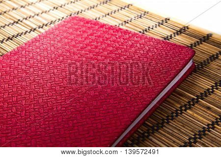 Red leather notebook on bamboo mat on white background