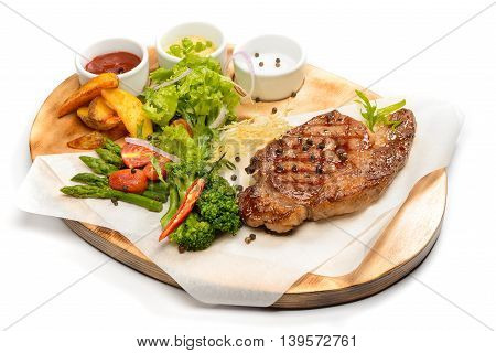 Steak with vegetables and sauce on wooden plate