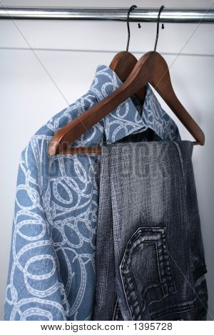 Blue Jeans And Shirts On Wooden Hangers