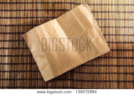 Brown vintage bamboo wood mat background texture with vintage paper in center