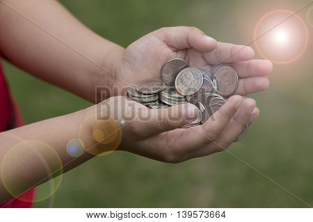 hand with coin isolated against a green background
