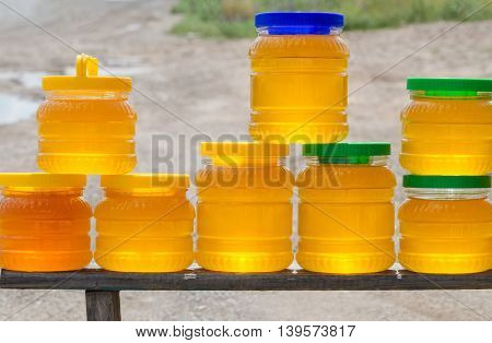 Different varieties of honey in plastic banks for sale beside the road