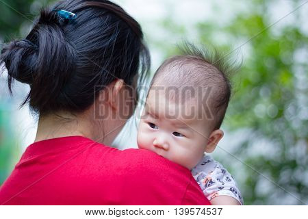 Mother And Baby, Lovely Asian Girl Resting On Her Mother's Shoulder. Mother's Day Celebration.