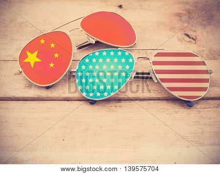mirror glasses with American and Chinese flag pattern on wooden background vintage filter effect.