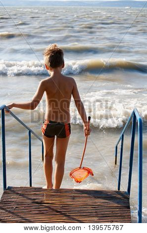 Young boy standing on stairs at the beach with a landing net