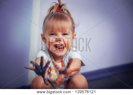 Little Girl with drawings on the face shows his hands in paint