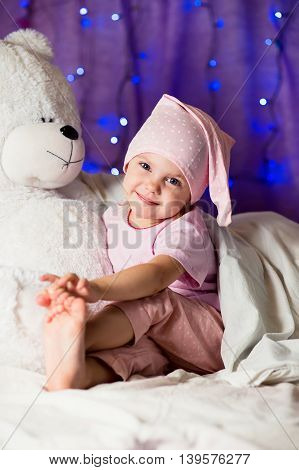 smiling little girl sitting on the bed in pink pajamas in the nightcap on a purple background with Christmas lights