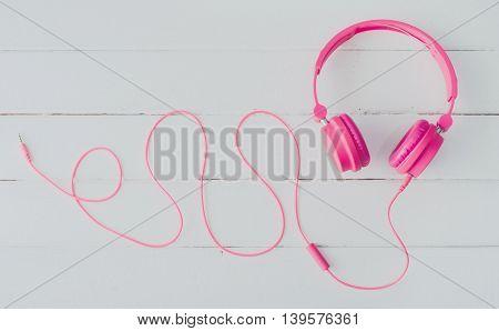 Pink headphones on the white wooden floor