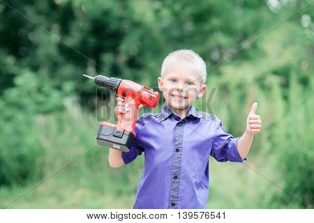 little blond boy of five years on the street in a blue shirt with the sleeves rolled up screwdriver hands (with a drill) smiling
