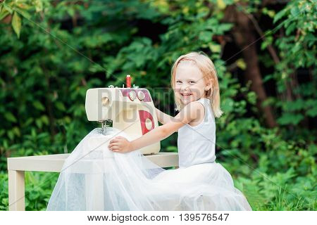 little blonde smiling lovely child 4 years old (girl) in a white skirt of tulle tutu dress sews on the sewing machine in the street