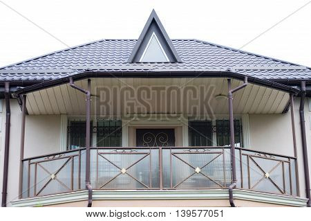 The top of the beige color house with the balcony on the second floor isolated on white background