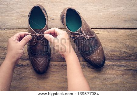 Hands of a young man shoelace on wooden floor
