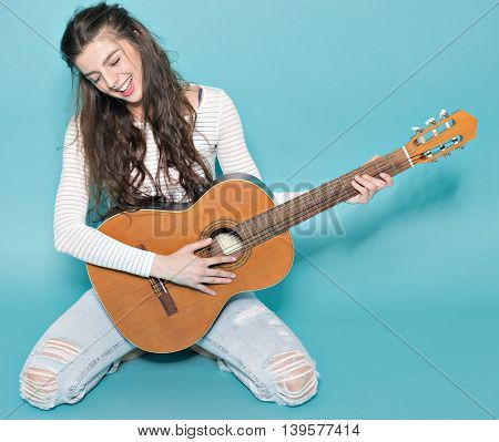 smiling beautiful young girl posing with guitar