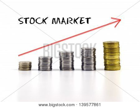 Conceptual Image. Stacks Of Coins Against White Background With Red Arrow And Stock Market Words.
